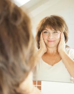 older woman looking in mirror