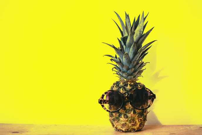 green pineapple fruit with brown framed sunglasses beside yellow surface