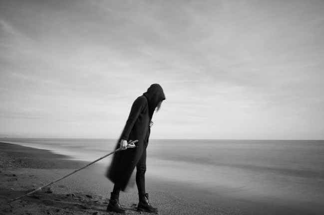 woman in black cloak with fishing pole standing in beach