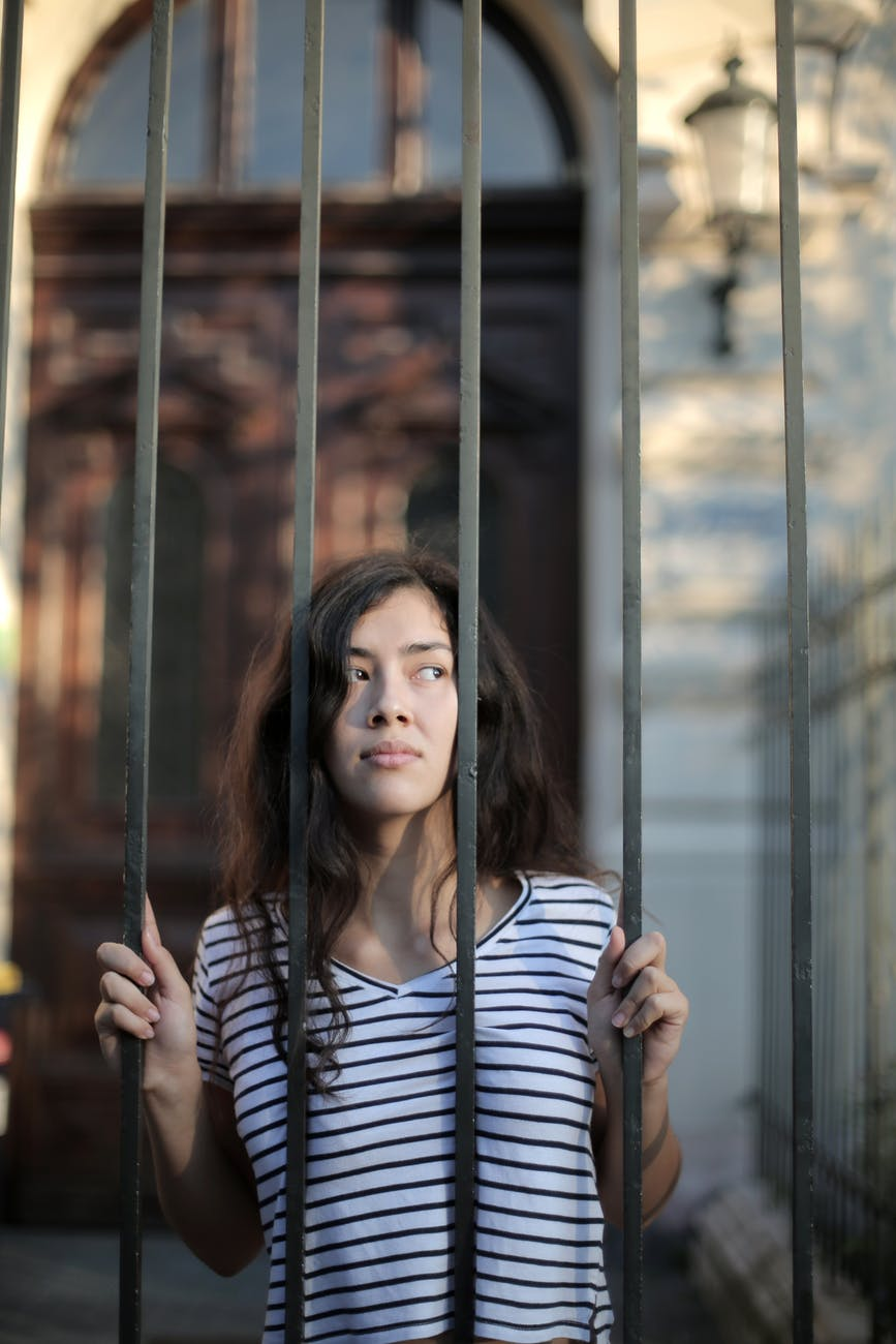 curious isolated young woman looking away through metal bars of fence with hope at entrance of modern building